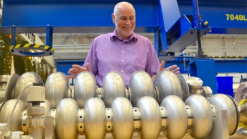 Andrew Hutton, associate director of Jefferson Lab's Accelerator Division, looks over prototype particle accelerating devices – called cavities – in the lab's Superconducting Radiofrequency Institute.