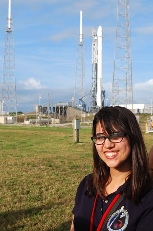 Emily Martinez stands in front of the Falcon 9 rocket before her experiment launches to the International Space Station.