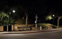 Photo of a sidewalk at night with a bench in the middle and streetlights on either side.
