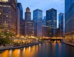 Photo of a city's downtown, with lots of tall office buildings, and a river in the foreground.