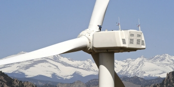 A wind turbine with mountains in the background.