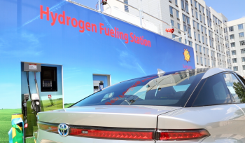 A fuel cell vehicle drives by a dmonstration building painted with the words Hydrogen Fueling Station.