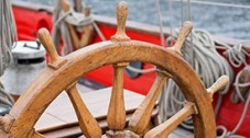 Photo of the wheel and helm of a boat.