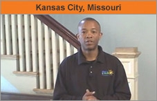 "A man standing at a residential staircase, with the words ""Kansas City, Missouri."""