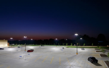Photo of a parking lot at night with lights on.