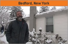 "A man standing outside a house in wintertime, with the words ""Bedford, New York."""