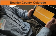 "Torso of a man holding a computer tablet with the words ""Boulder County, Colorado."""