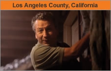 "A man working inside a house, facing the camera, with the words ""Los Angeles County, California."""