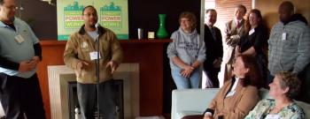 Photo of a small group of people in the living room of a home listening to a man speaking at a microphone.