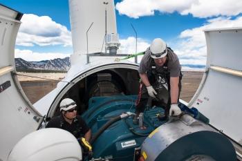 A wind technician inspects a wind turbine.
