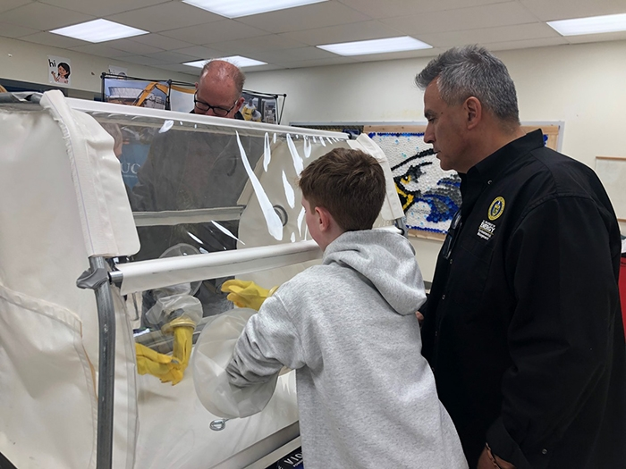 James Nunz, project management branch chief for Oak Ridge's EM program, teaches students how to use a glovebox during a demonstration at the STEM event.