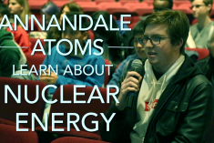 A student with a microphone asks a question during a visit from the Department of Energy.