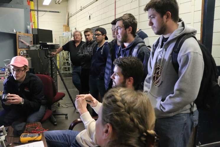 A group of Pennsylvania State University students watch a wind tunnel testing.