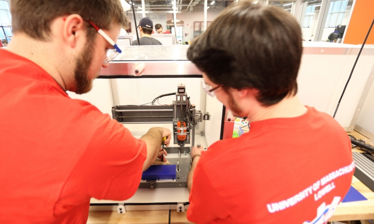 Team UML-WindHawk (from left to right): E. Copeland, and C. Illsley using on a desktop CNC machine to create a wind turbine blade mold.