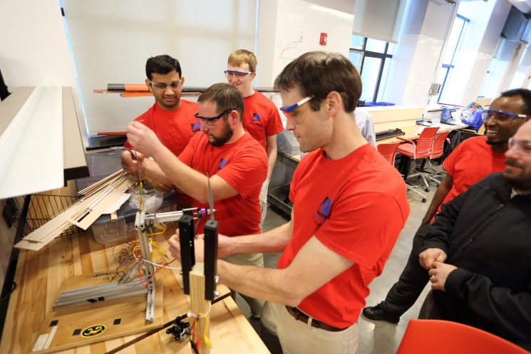 The UML-WindHawk electrical team. (from left to right):N. Patel, M. Siopes, K. Stuart, W. Hallissey, M. Barre,S. Dabney working on the electrical generator test bed.