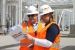 Pump-and-treat construction managers David Fink (left) and Delise Pargmann (right) review information for the LEED gold certification of the main process building for the 200 West Groundwater Treatment Facility.