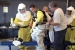 Trainers adjust a Plutonium Finishing Plant employee's harness that carries the respirator, cooling system, and other equipment safely inside the protective suit.