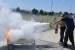 A Hanford site volunteer helps a Boy Scout practice the Pull, Aim, Squeeze, Sweep, or PASS, fire extinguishing technique at the Volpentest HAMMER Training & Education Center in Richland.