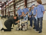 """Tennessee Governor Bill Haslam signs the robot of Hardin Valley Academy's FIRST robotics team during the dedication of DOE's Carbon Fiber Technology Facility, located at Oak Ridge National Laboratory. The RoHAWKtics team (named after their school mascot) spent an intense six weeks constructing the robot, using design, engineering, and problem-solving skills. The team will be moving on to a national competition in April. Learn more about the <a href=""""http://www.ornl.gov/info/features/get_feature.cfm?FeatureNumber=f20130401-00"""">FIRST competition</a>.   Photo courtesy of Oak Ridge National Laboratory."""
