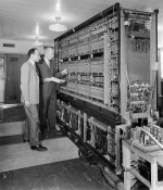 "In this photo, two Argonne researchers are pictured with Argonne's first digital computer, AVIDAC. Designed and built by Argonne's Physics Division for $250,000, it began operations on January 28, 1953. AVIDAC stands for ""Argonne Version of the Institute's Digital Automatic Computer"" and was based on architecture developed by mathematician John von Neumann. Groundbreaking as it was, today's smartphones are far more sophisticated and powerful than this machine. 