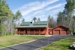 Sistine Solar's completed SolarSkin installation on a Katahdin log cabin. The company's SolarSkin panels seamlessly blend in with the cabin's green roof. | Photo Courtesy of Sistine Solar