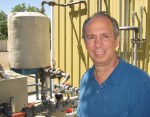 Pictured here is Michael Brambley in front of equipment that supplies chilled water to PNNL Building Diagnostics Laboratory's air handler. The cooled air from an air handler is distributed to terminal boxes, which are the last point for controlling air temperature and flow before distributing it throughout a building zone. In a new control strategy for commercial buildings, the terminal boxes would process the information collected by occupancy sensors to control the air handler's fan speed for energy savings. | Photo courtesy of Kristin Nolan, freelancer.