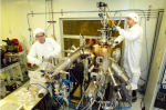 Inside a clean room, Brookhaven physicists Ivan Bozovic (left) and Anthony Bollinger work on the molecular beam epitaxy system that produced the atomically perfect materials used in the study.   Photo courtesy of Brookhaven National Lab