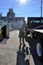 A Centerra Protective Force employee uses a mirror to check the undercarriage of a transport trailer before it enters a Savannah River Site Limited Area.