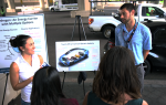 Two people stand in front of posters about fuel cell electric vehicles.