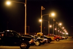 Photo of a parking lot at night with cars parked and lights lit overhead.