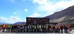 Employees hold signs denoting the milestone of relocating 9 million tons of uranium mill tailings from the Moab Site.