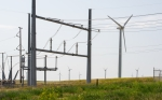 Electrical transmission lines in a field next to a wind turbine.