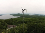 A small wind turbine in a wooded area by a lake.