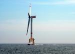 Photo of a wind turbine at sea.