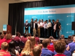 A student team in the Collegiate Wind Competition stands on stage in front of a banner at the WINDPOWER conference.