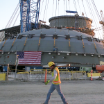A photo of man walking by the top of a containment structure for a nuclear reactor
