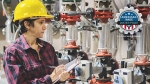 Woman wearing a hard hat and holding a clipboard assesses machinery.