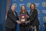 Ambassador Linton Brooks, left, and NNSA Administrator Lisa Gordon-Hagerty, right, present the 2019 Linton Brooks Award to Jessica Lillo.