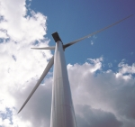 View of a wind turbine from below against a blue sky.