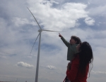 A NREL employee's daughter points at the turbines while in her mother's arms at the National Wind Technology Center.