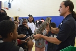 Sean Poppy, outreach coordinator for the University of Georgia's Savannah River Ecology Laboratory outreach program, shows a juvenile alligator to students at Blakeney Elementary School in Waynesboro, Georgia.