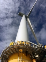 View of an offshore wind turbine from underneath against a cloudy sky.