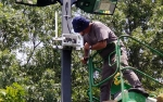 Photo of a man in a bucket truck looking at outdoor lighting controls.