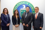Speakers stand in front of the DOE seal