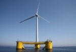 Photo of a wind turbine on a yellow floating platform in the ocean.
