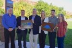 Officials hold plaques representing the Moab Uranium Mill Tailings Remedial Action (UMTRA) Project's progress moving waste to a permanent disposal cell.