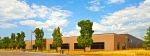 The Clarios Meadowbrook facility. A brown brick building, with trees in front of it.
