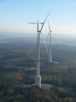 During construction, workers climb out on top of a tall wind turbine and guide 19-ton turbine blades into place.