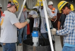 Workers test a modified cutting tool in a mock demonstration before using it to modify storage positions for waste canisters inside the Glass Waste Storage Building 1.
