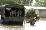 Military personnel rescuing residents from a flooded area